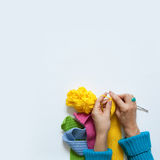 Woman knitting needles colored fabric. View from above. White ba Royalty Free Stock Photos