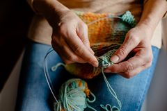 Woman Knitting a scarf with colorful melange threads. Woman Knitting a scarf. Hands holding threads. Colorfull Knitting with colorful melange threads stock photography