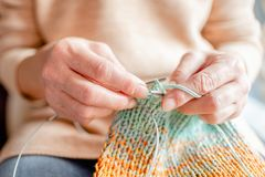 Woman Knitting a scarf with colorful melange threads. Woman Knitting a scarf. Hands holding threads. Colorfull Knitting with colorful melange threads royalty free stock image