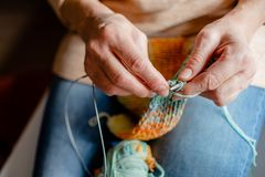 Woman Knitting a scarf with colorful melange threads. Woman Knitting a scarf. Hands holding threads. Colorfull Knitting with colorful melange threads stock photo