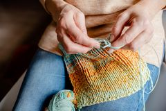 Knitting a scarf with colorful melange threads. Woman Knitting a scarf. Hands holding threads. Colorfull Knitting with colorful melange threads royalty free stock photography