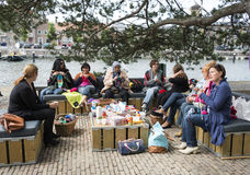 Woman knitting on a sofa outside on multiculture day in holland