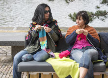 Woman knitting on a sofa outsideon multiculture day in holland