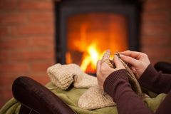 Woman knitting warm wool socks in front of fireplace - closeup Royalty Free Stock Image