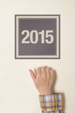 Woman knocking on door with number 2015. Happy New Year conceptual image, celebration at the door Royalty Free Stock Photography