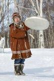 Woman in Koryak national dress dancing, beats the tambourine and singing. KAMCHATKA, RUSSIA - FEB 5, 2012: Woman in Koryak national dress dancing, beats the stock image