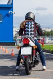 Woman L-driver is ready for driving slalom on training ground on motorbike Stock Image