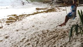 Woman at La Digue swing. Slow motion: elegant tourist woman with blue dress on swing under tropical trees and enjoying the beach Anse Severe in La Digue stock footage