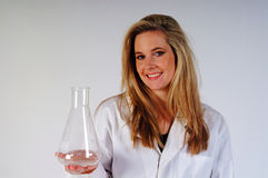 Woman in Lab coat. Young woman in lab coat holding a glass beaker Stock Photos