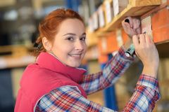 Woman labelling shelf under pallet in warehouse. Pallet Stock Photography