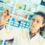 Woman laboratory assistant draws a graph on  glass Stock Photography