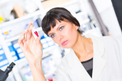 Woman in a laboratory with microtube test tube  in hand and PCR Royalty Free Stock Photos