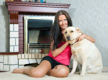 Woman with  Labrador retriever. Mid adult woman with  Labrador retriever near the  electric fire Royalty Free Stock Photo