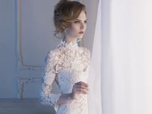 Woman in lace dress at the window Stock Photos