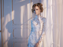 Woman in lace dress at the window Stock Photo