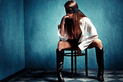 Woman with lace over eyes. Sensual young woman with lace covering eyes sit on chair in shirt and leather boots Royalty Free Stock Photo
