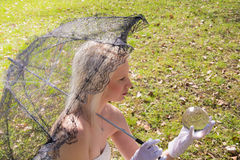 Woman with lace umbrella and glass ball Stock Photography