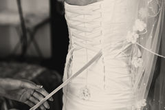 Woman lace up a corset on the delicate bride's waist Stock Photo