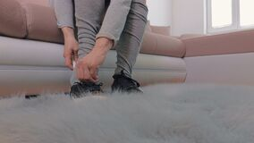 Woman lace up sneakers. In room stock video footage