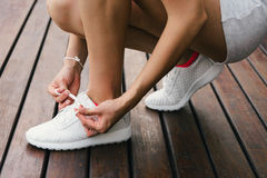 Woman lacing fitness footwear Stock Photography