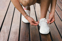 Woman lacing fitness footwear Stock Image