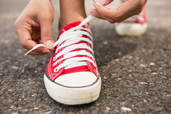 Woman lacing her shoes before jogging in park Royalty Free Stock Image