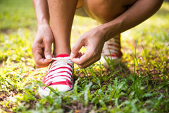 Woman lacing her shoes before jogging in park Stock Photo