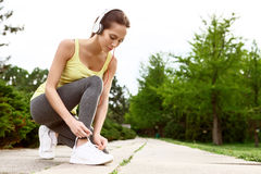 Woman lacing her shoes in park Stock Images