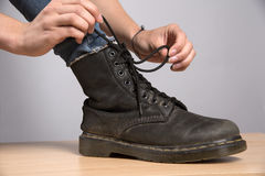 Woman lacing up a black boot Stock Image