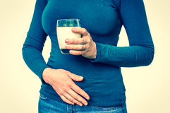 Woman with lactose problem is suffering from stomach pain. On white - dairy intolerance concept - retro style Royalty Free Stock Photo