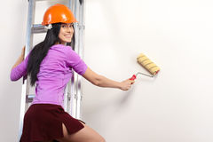Woman on ladder painting Stock Images