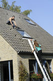 Woman on ladder and roofer working on a roof Royalty Free Stock Photography