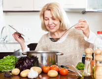 Woman with ladle cooking soup in pan  in home kitchen Royalty Free Stock Photography