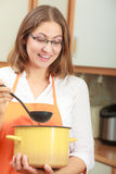 Woman with ladle and pot in kitchen Stock Photos