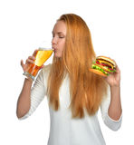 Woman with lager beer mug and burger sandwich hamburger in hands Stock Images