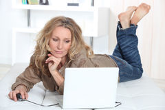 Woman laid in front of a laptop Stock Photography