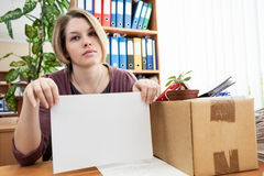 Woman, laid off at work, holding white paper Royalty Free Stock Photography