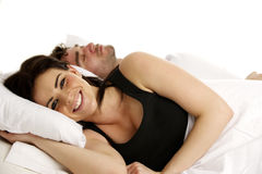 Woman laid smiling in white bed next to a sleeping man Stock Photo