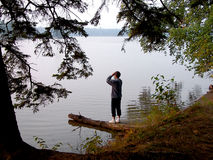 Woman beside lake. Woman gazing out over northern lake with binoculars Royalty Free Stock Photography