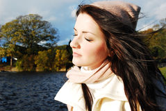 Woman by a lake. A brunette young woman by a lake with her eyes closed. Suggests contentment/happiness Stock Photography