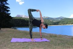 Woman with lake in the background. Woman practicing yoga on  with lake in the background. The picture was taken on Zabljak municipiun. The model was certificated Royalty Free Stock Photos