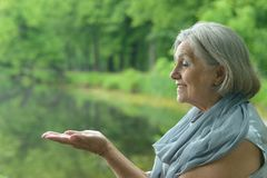 Woman at lake. Beautiful happy elderly woman relaxing at lake Royalty Free Stock Photos