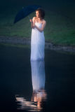 Woman on the lake bed sheet wrapped royalty free stock image