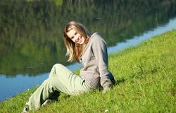 Woman on lake edge. Photo of a happy woman...lin in grass royalty free stock photo
