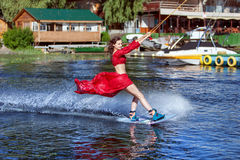Woman on the lake goes for a wakeboard ride. Woman enjoys skating on the lake on a wakeboard Stock Photo