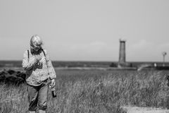 Woman At Lake Michigan. Dramatic shot of a woman showing emotion with the lake and lighthouse behind her royalty free stock photography