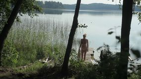 Woman on the lake on the pier. A woman stands on the pier on the lake. She puts a towel on her shoulder. Around the pine forest. Counter light stock video