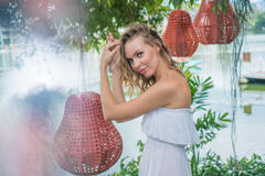 Woman by the lake. Pretty blond woman in sexy white summer dress looking and smiling at the camera standing between beautiful lights hanging from the trees Royalty Free Stock Images
