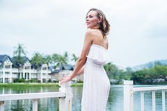 Woman by the lake. Pretty blond woman in sexy white summer dress standing on the pier and smiling against beautiful lake and tropical resort background Royalty Free Stock Photos
