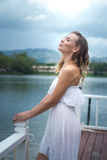 Woman by the lake. Pretty blond woman in sexy white summer dress standing on the pier and smiling against beautiful lake and tropical resort background Stock Image